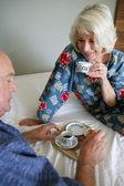 Senior couple having breakfast in bed — Stock Photo