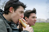 Teenage boy eating sandwich outdoors — Stock Photo