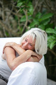 Grey haired woman relaxing on a garden sofa — Stock Photo