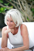 Grey-haired woman sat in the garden — Stock Photo