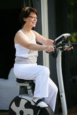 Woman working on exercise bike — Stock Photo