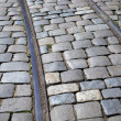 Tram tracks running through a cobbled street - Stock Photo