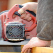 Stock Photo: Carpenter using a circular saw