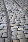 电车轨道运行通过一条鹅卵石铺成的街道 — 图库照片