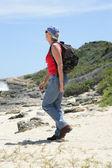 Vrouw wandelen langs de kust — Stockfoto