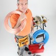 Stock Photo: Plumber holding copper piping with various other materials