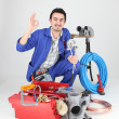 Stock Photo: Plumber surrounded by equipment