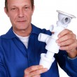 Stockfoto: Plumber holding replacement part