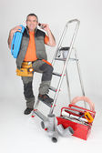 Plumber on the phone next to stepladder — Stock Photo
