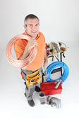 Plumber holding copper piping with various other materials — Stock Photo