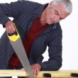 Mature carpenter using saw — Stock Photo