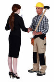 Businesswoman and craftsman shaking hands — Stock Photo