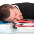 Businessman asleep on a pile of paperwork — Stock Photo