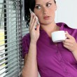 图库照片: Womwith telephone and coffee cup