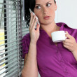 Foto Stock: Womwith telephone and coffee cup