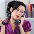 Woman dealing with two phone calls — Stock Photo