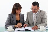 Man and woman studying a book together — Stock Photo