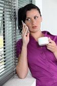 Mujer con teléfono y café taza — Foto de Stock