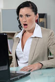 Businesswoman looking at her laptop open mouthed — Stock Photo