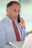 Mature businessman on the phone looks stunned — Stock Photo