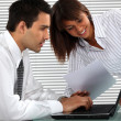 Office couple with a laptop — Stock Photo
