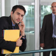 Businessman looking at male colleague in workplace — Stock Photo