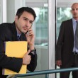 Businessman looking at male colleague in workplace - Stock Photo
