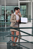Businesswoman on the phone outside an office — Stock Photo