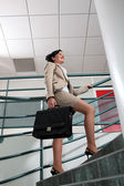 Businesswoman with briefcase climbing stairs — Stock Photo