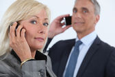 Mature business couple using cellphones — Stock Photo