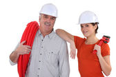 Senior craftsman and young craftswoman posing together — Stock Photo