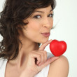 A brunette woman and a little red plastic heart — Stock Photo