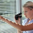 Woman looking through the blinds with binoculars - Stock Photo