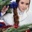Young woman stood by Christmas tree — Stock Photo