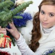 Young woman under a Christmas tree - Stock Photo
