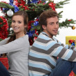 Portrait of cute young couple sitting back to back at Christmas time — Stock Photo