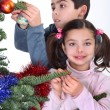 Children decorating Christmas tree — 图库照片