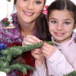 Mother and daughter decorating Christmas tree - 