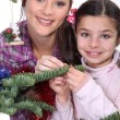Mother and daughter decorating Christmas tree - Stock Photo