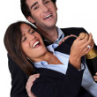 Laughing business couple celebrating with champagne — Stockfoto #16017231