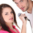 Stock Photo: Young couple singing into microphone