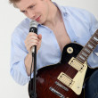 Man playing electric guitar and singer — Stock Photo
