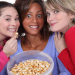 Peppy women eating popcorn — Stock Photo