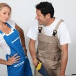 Stock Photo: Amused womwatching mas he is sawing plank.