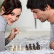 Cute young couple playing chess together — Photo