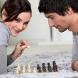 Cute young couple playing chess together — 图库照片