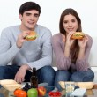 Stock Photo: Young couple eating hamburgers