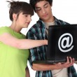 Teens with black computer — Stock Photo
