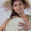 Stock Photo: Womwearing straw hat and playing djembe