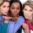 Stock Photo: Three attractive women blowing kisses